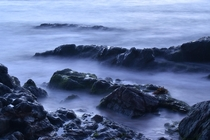 Long exposure of water between rocks before sunrise Korora Bay Coffs Harbour Australia