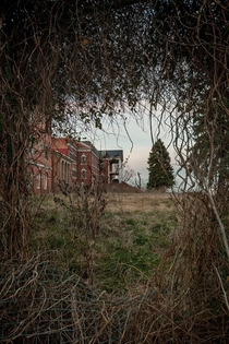 Looking through a hole in the fence at the Abandoned DeJarnette Childrens Sanitarium in Virgina Photo by Tom Kirsch