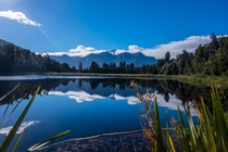 Lucky break in the clouds before the water ripples covered the surface Lake Matheson NZ