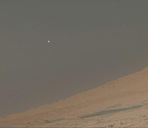 Martian Moonrise an afternoon shot of the moon Phobos over the northern limb of Mount Sharp