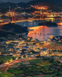Massive industrial port seen across the bay from a sleepy fishing village in Yeosu South Jeolla Province South Korea
