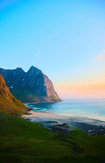 Midnight sun on remote beach Lofoten Norway
