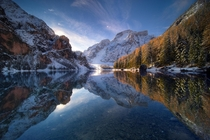 Mirror reflection on Lago di Braies during a cold sunrise in November - Dolomites Italy
