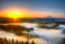 Mist covers the valley below as the sun rises over Jonsrud Viewpoint Oregon