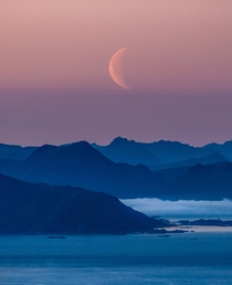 Moonrise over the distant peaks of Lofoten