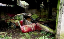 Moss-covered car in garage of abandoned house in British countryside