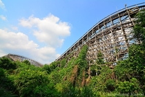 Mostly overgrown wooden rollercoaster Aska at the abandoned Nara Dreamland