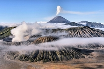 Mount Bromo in foreground and Mount Semeru in background on a misty morning in East Java Indonesia Achmad Sumawijaya