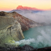 Mount Ijen smoking while Mount Raung erupts in the background at sunrise East Java Indonesia