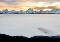 Mount Moran and the Teton Range in the background with a mostly frozen Jackson Lake in the foreground Grand Teton on the far left