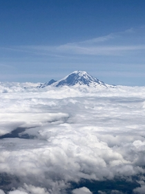 Mount Rainier peeking through the clouds Taken from my plane seat over Seattle Washington