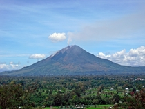 Mount Sinabung in Sumatra Indonesia with villages in the foreground
