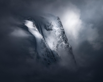 Mountain peeking through some heavy clouds in Nordfjordeid Norway