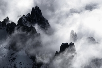 Mountains peaks wrapped in clouds ine the Dolomites
