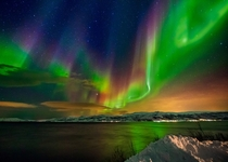 Multi-colored Aurora Borealis and a starry night sky over Troms Norway  by Wayne Pinkston x-post rNorwayPics