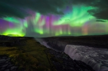 Multicolored Lights of the Aurora Borealis over Dettifoss a gigantic waterfall in Northern Iceland -  OC