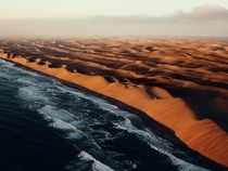 Namibia on Africas southwest coast is a large country with a harsh landscape The towering and constantly shifting dunes of the Namib Desert shown here in this aerial photo by Julian Walter run right to the Atlantic Ocean and can reach up to a thousand fee