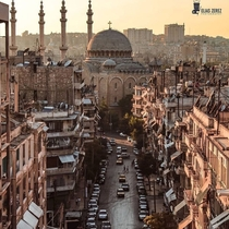 Narrow streets in Aleppo syria pictured in the photo is the cathedral of saint georgios and the minarets of the tawhid mosque