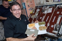 NASA astronaut Michael Hopkins Expedition  flight engineer poses for a photo with his Thanksgiving meal in the Unity node of the International Space Station Nov