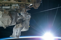 NASA astronaut Terry Virts Flight Engineer of Expedition  works to complete a cable routing task while the sun begins to peek over the Earths horizon on the International Space Station -