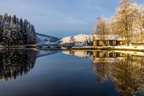 Norwegian cabins reflect in the water on a crisp day  Photographed by Richard Larssen