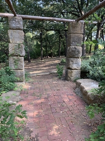 Not totally abandoned but in the process of being forgotten This is a memorial garden in Denison TX The hospital that erected it was moved and the old hospital torn down The stone columns and brick have significance And the grapevines are gone and creek d