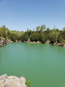 OC A stone quarry hidden deep within the back roads of Kentucky USA The water is so clear but at over ft deep youll never see the bottom x