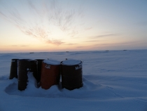 Oil barrels in the frozen wilderness Inuvik Region NT Canada