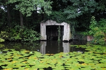 Old boat house at the far end of the lake surrounded by lily pads