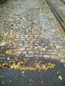Old Boston street paved in cobbles setts and asphalt concrete