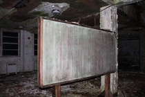 Old decayed chaulk board inside of a boys boarding school