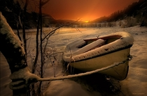Old row boat tied off at the rivers edge in a winter landscape with a sunset in the background Photo by Wim Lassche