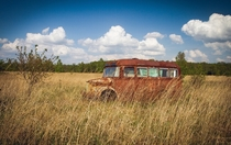 Old Rusted Bus in a Field  by R Alina Photography