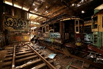 Old tramcars and trolley buses sit abandoned and wrecked in the Loftus Tram Shed in Sydney Australia