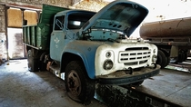 Old trucks are left in abandoned workshops