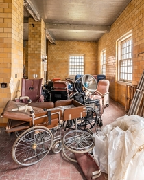 Old wheelchairs piled in a corner of a room inside an abandoned state hospital