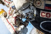 Oleg Kononenko spacesuit with red stripes and Sergei Prokopyev spacesuit with blue stripes examining the hole in Soyuz spacecrafts orbital module