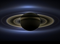 On July   in an internationally celebrated event NASAs Cassini spacecraft slipped into Saturns shadow and turned to the image of the planet seven of its moons  its inner rings - and in the background our home planet Earth
