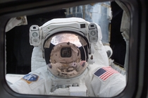 Orbiting high above Earth NASA Astronaut John M Grunsfeld peers into the crew cabin of the Space Shuttle Columbia during the first STS- extravehicular activity EVA- on March   The photo was snapped with a digital still camera by a crewmate on shuttles aft