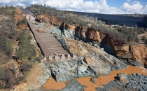 Oroville Dams -foot-long spillway including massive damage started by a cave-in and increased by an emergency release of water in Feb