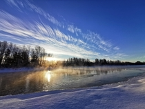Painted clouds and blue winter sky over steaming river in Qubec
