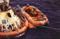 Pararescueman Lt Clancy Hatleberg closes the Apollo  spacecraft hatch as astronauts Neil Armstrong Michael Collins and Buzz Aldrin Jr await helicopter pickup from their life raft They splashed down on July    miles southwest of Hawaii after a successful l