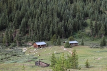 Partially reconstructed gold sifter cabins in a valley outside of Aspen CO With the Continental Divide in the background