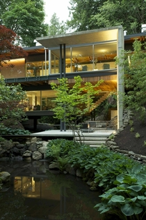 Patio next to elevated living areas with glass walls overlooking the lush vegetation surrounding a pond DunbarSouthlands Vancouver Canada