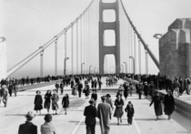 Pedestrians walk across the Golden Gate Bridge on opening day May
