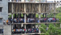 People gather in a neighboring under-construction building to watch the rescue operation of the collapsed Rana Plaza building  km  miles outside Dhaka on April   ReutersStringer