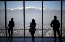 People look out to the Los Andes mountain range next to the city from a rooftop of a commercial center in Santiago Chile Ivan Alvarado