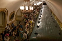 People waiting for subway train to come to a halt incredibly ornate Moscow subway station  Summer