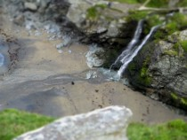 photo from near the top of tintagel castle of the waterfall on the beach bellow in camera tilt-shift toy town effect from my little handbag camera