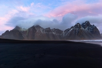 Pink hues stretch above the mountains of Vestrahorn Iceland   x